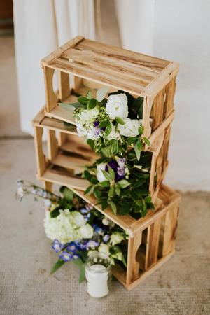 Houten kratten met bloemen en kaarsen. Bruiloft decoratie.