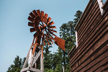Oude roestige windmolen met blauwe hemel op achtergrond Stockfoto