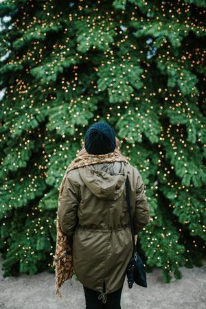 Vrouw die zich voor grote Kerstboom bevindt