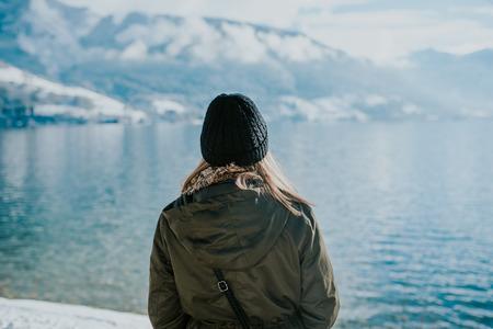 Vrouw die zich op lakeshore met sneeuwbergen op de achtergrond bevindt