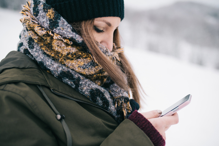 Vrouw die mobiele smartphone openlucht in de winter gebruiken