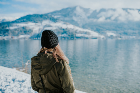 Woman standing on the lakeshore with snowy mountains in the background