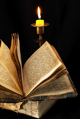 old religious book and candle on black background, photo