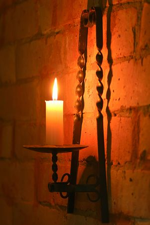glow stick: Candle in brass holder lighting wall of brick