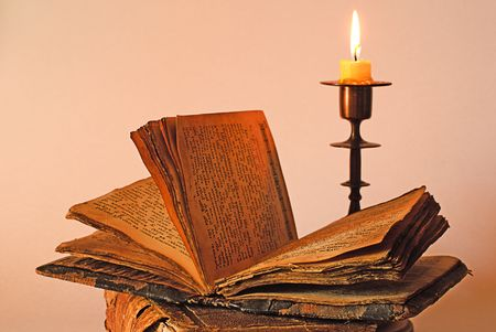 old religious book and candlestick with candle photo
