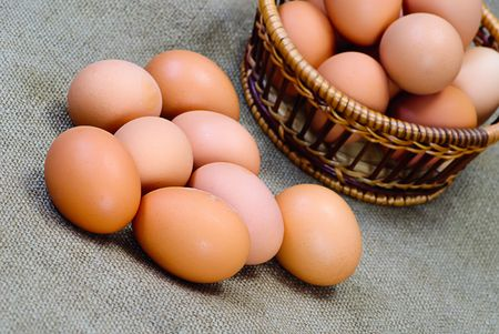 new-laid eggs Chicken eggs of brown color in wooden basket photo