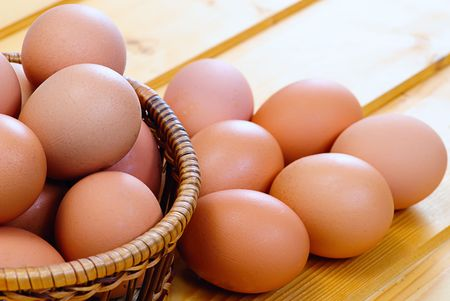 new-laid eggs Chicken eggs of brown color inwooden basket photo