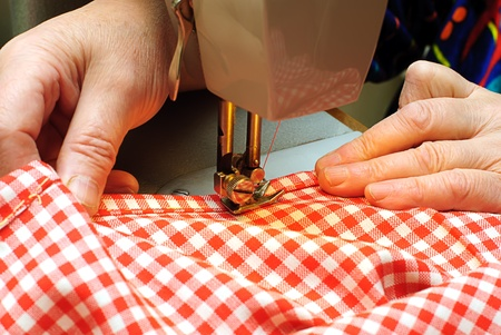 stitching machine:  Hands stitching denim cloth with a sewing machine