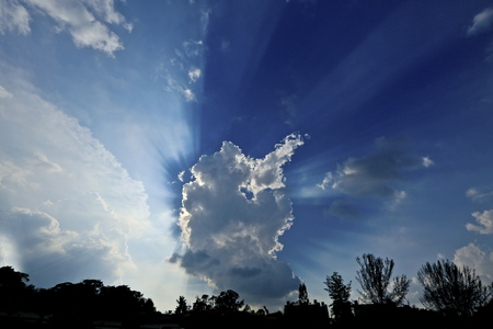 The light of the sun penetrate the clouds and darkness at open sky.