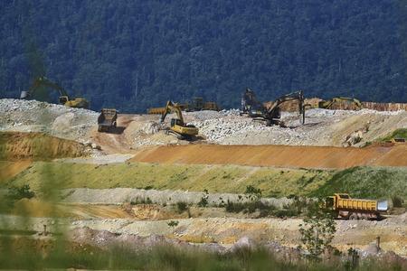 Excavators and ground trucks do the work of slashing down the hillside
