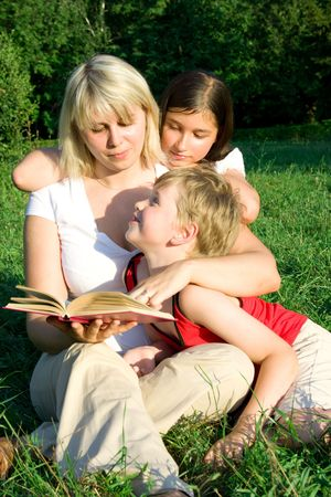 The young woman sits on a grass and reads the book to the children photo