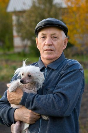 Portrait of the elderly man with a dog of breed chinese crested against the nature