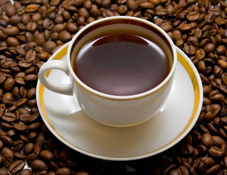Cup with hot coffee on a coffee beans background Stock Photo