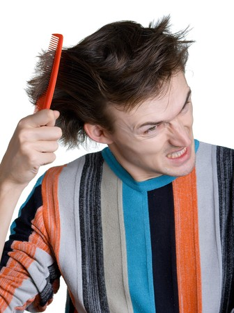 The aggressive young man with the hairbrush which has got stuck in shaggy hair. Isolation on a white background