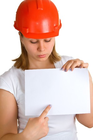 The young women in a red building helmet shows on a sheet of paper in a hand. Isolation on a white background Stock Photo - 4504568
