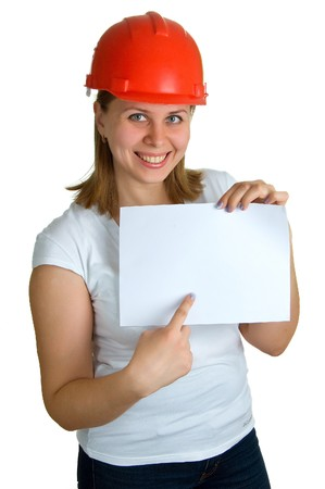 The young smiling women in a red building helmet shows on a sheet of paper in a hand. Isolation on a white background Stock Photo - 4536388