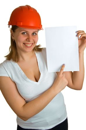 The young smiling women in a red building helmet shows on a sheet of paper in a hand. Isolation on a white background Stock Photo - 4723464