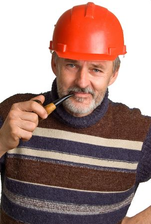 superintendent: Elderly smiling men in a red building helmet with a pipe in a hand. Isolation on a white background