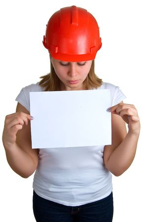 The young women in a red building helmet holding a sheet of paper in a hand. Isolation on a white background Stock Photo - 4922919