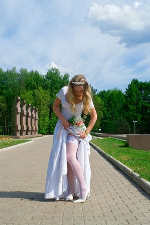 corrects: bride in a white wedding dress corrects a stocking in park