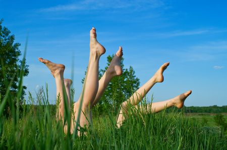 Feet of girls laying and sunbathing in a grass against the blue summer sky