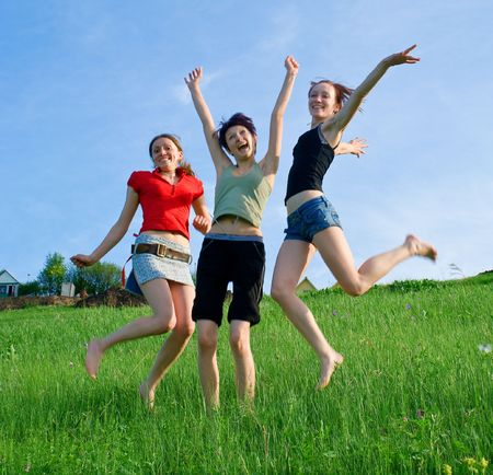 Girls jump on the meadow against blue summer sky Stock Photo - 5022426