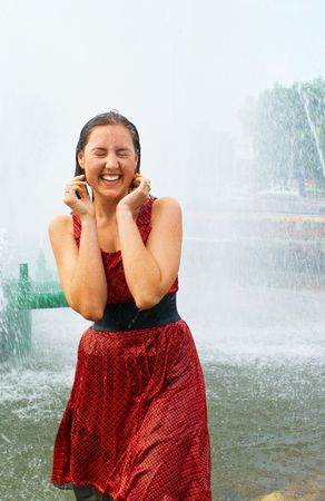 The young laughing girl in wet clothes in a city fountain Stock Photo - 5054961