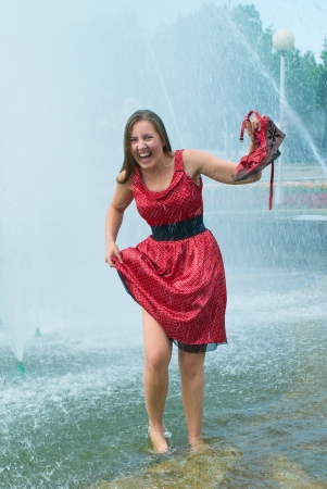 The young laughing girl in wet clothes in a city fountain Stock Photo