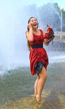 wet clothes: La muchacha r�e j�venes en la ropa mojada en una fuente de la ciudad