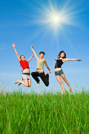 Girls jump on the meadow against blue summer sky