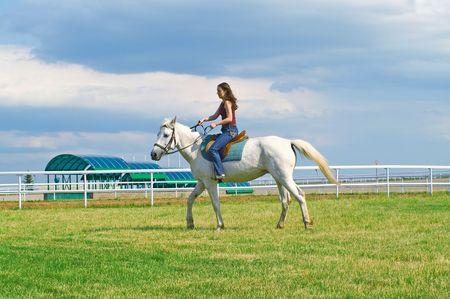 racehorses: Het jonge meisje van sereniteit schrijlings op een paard op een hippodroom  Stockfoto