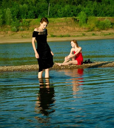 Two girls on the bank of the river. Summer landscape