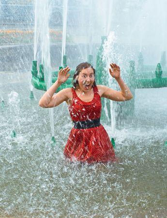 wet clothes: La joven sonriente en la ropa mojada en una fuente de la ciudad