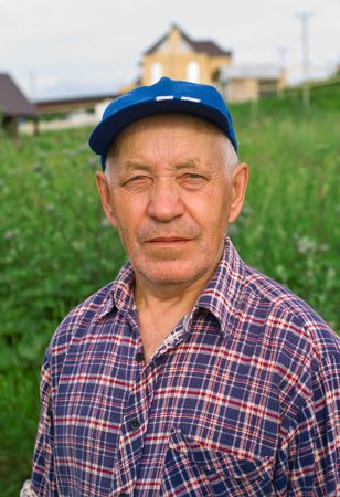 Portrait of the elderly man in cap against summer landscape
