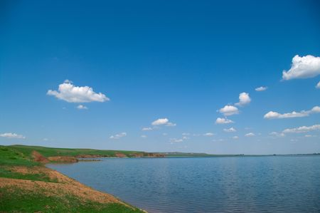 grazed: Summer landscape with quiet water of lake. The herd of cows is grazed on hills