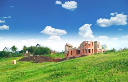 Not complete building of the private house against summer landscape with cloudy sky photo