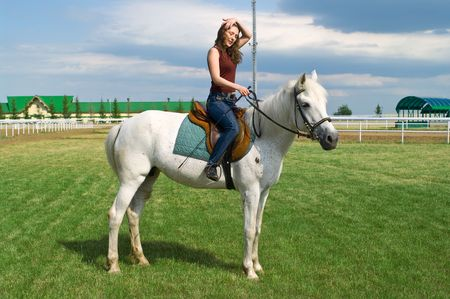 racehorses: The serenity young girl astride a horse on a hippodrome Stock Photo