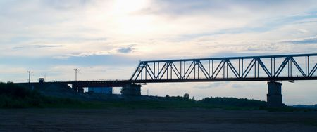The industrial bridge through the river against the sunset evening sky photo