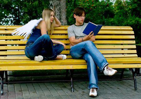 guardian angel: A los j�venes la lectura de un libro en un parque de verano. �ngel de la Guarda est� sentado a su lado Foto de archivo