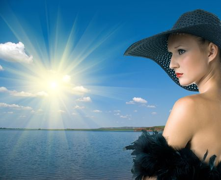 serenity women in black hat and boa against summer landscape with quiet water of lake