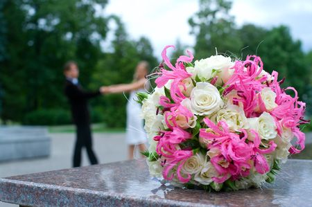 Wedding bouquet against young couple. Shallow DOF photo