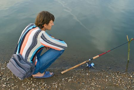 fishman: The young men fishes a fishing tackle in the river  Stock Photo