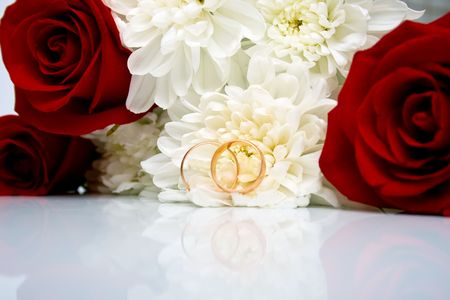 wedding rings, red roses and white chrysanthemumon. Shallow DOF photo