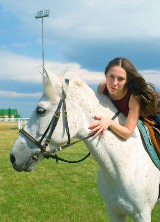 racehorses: Het jonge meisje van sereniteit schrijlings op een paard tegen blauwe hemel
