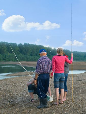 Young girls and men on fishing. A summer landscape with the river Stock Photo - 5850672