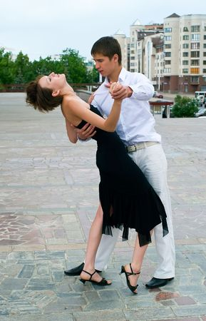 young couple dancing Latino dance against urban landscape