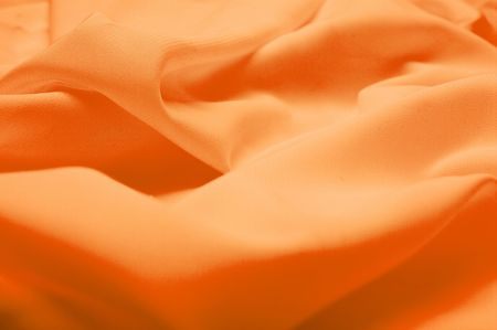 Abstract background. Orange silk fabric with waves. Shallow DOF Stock Photo