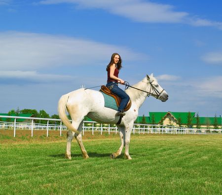 racehorses: The serenity young girl astride a horse against blue sky Stock Photo
