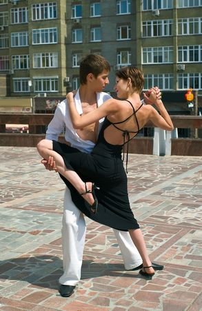 argentina dance: young couple dancing Latino dance against urban landscape