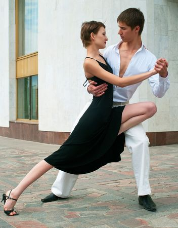 tangoing: young couple dancing Latino dance against urban landscape